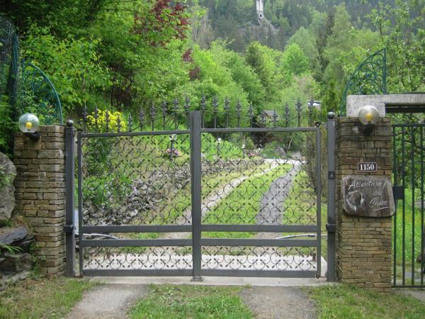 Portail en fer forgé qui ouvre sur le jardin